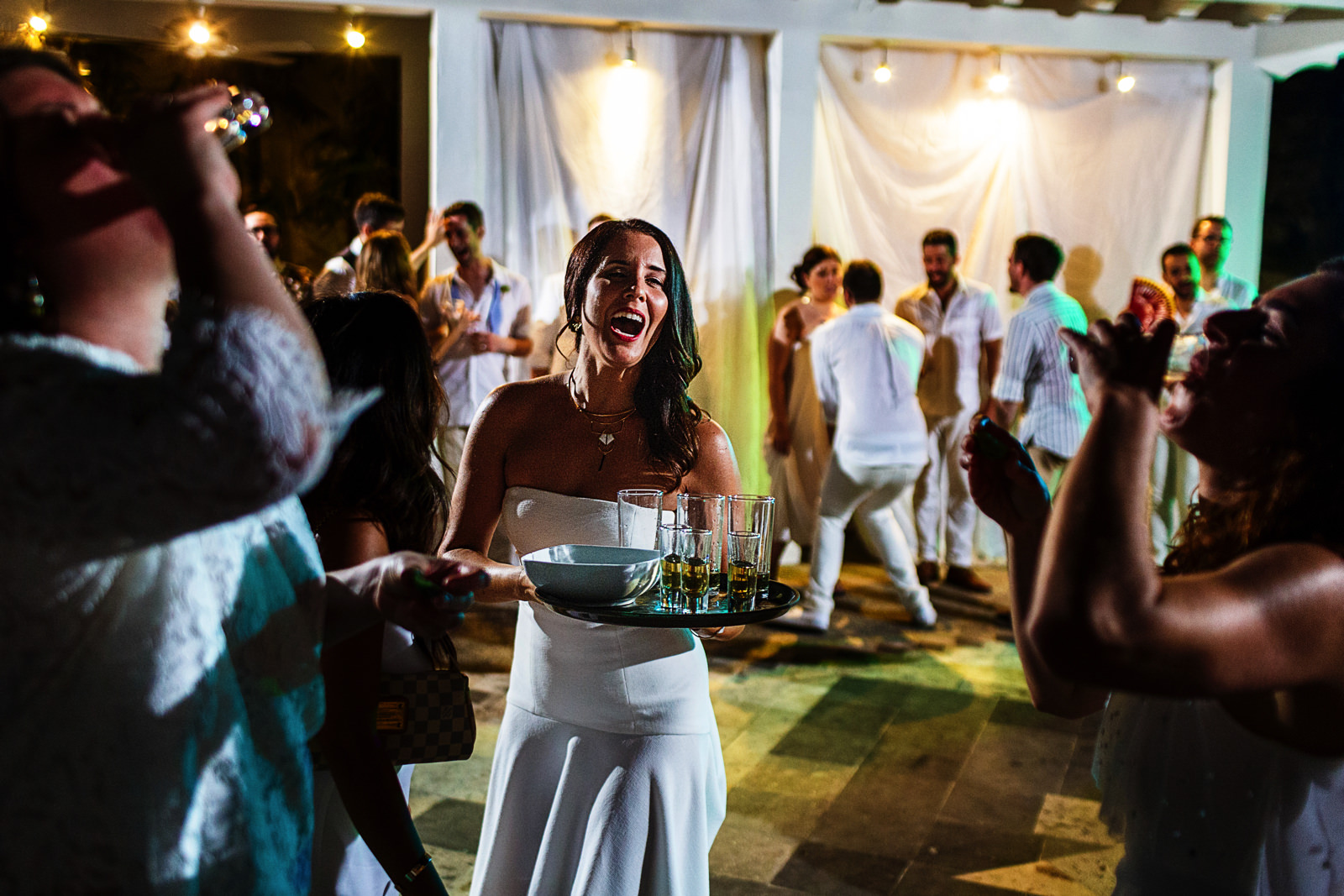 Wedding guest holds a tray of tequila shots while other two girls drink them