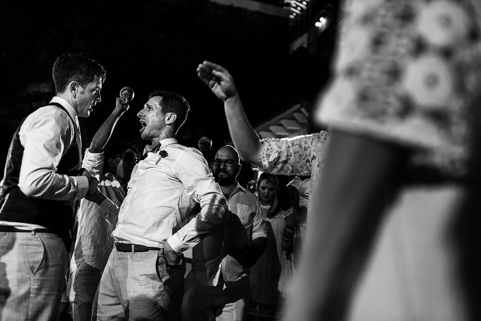 Grooms dance with guests at their wedding reception
