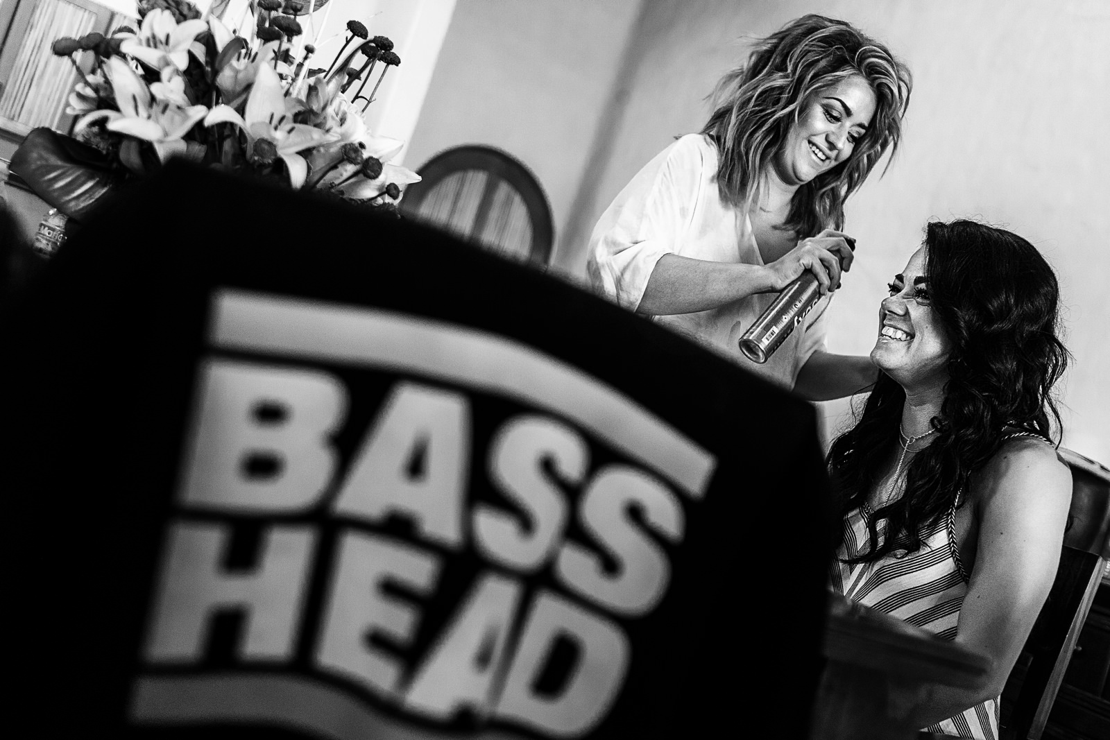 Two girls getting ready for a wedding and sharing a laugh, a BASS HEAD T-shirt is hanged over a chair in the foreground