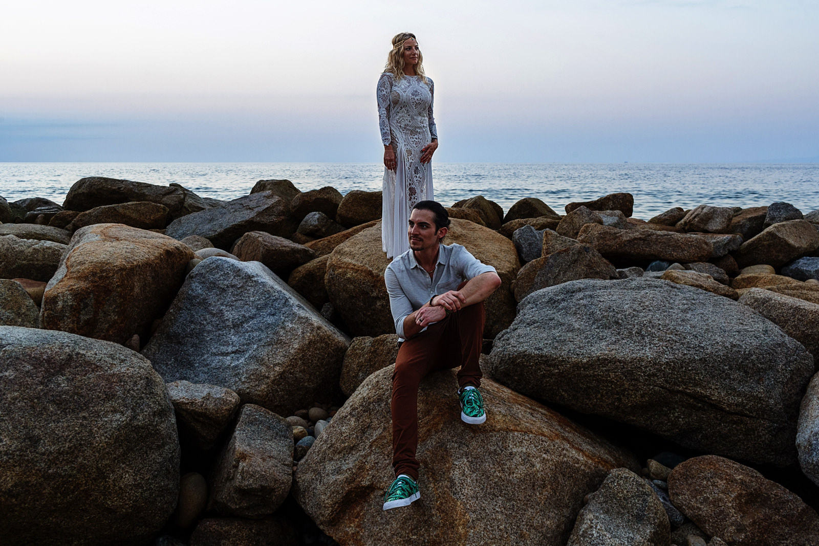 Wedding couple portrait, bride standing in the rocks while the groom is sitting on the rocks with the Mexican pacific ocean in the background