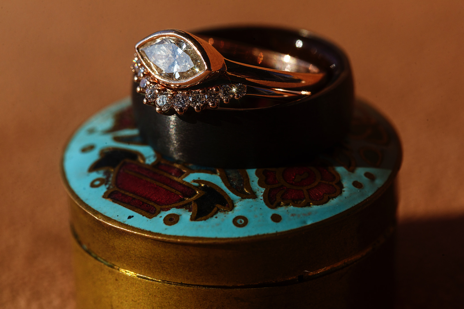 Wedding bands and engagement wedding ring on top of an antique circular box