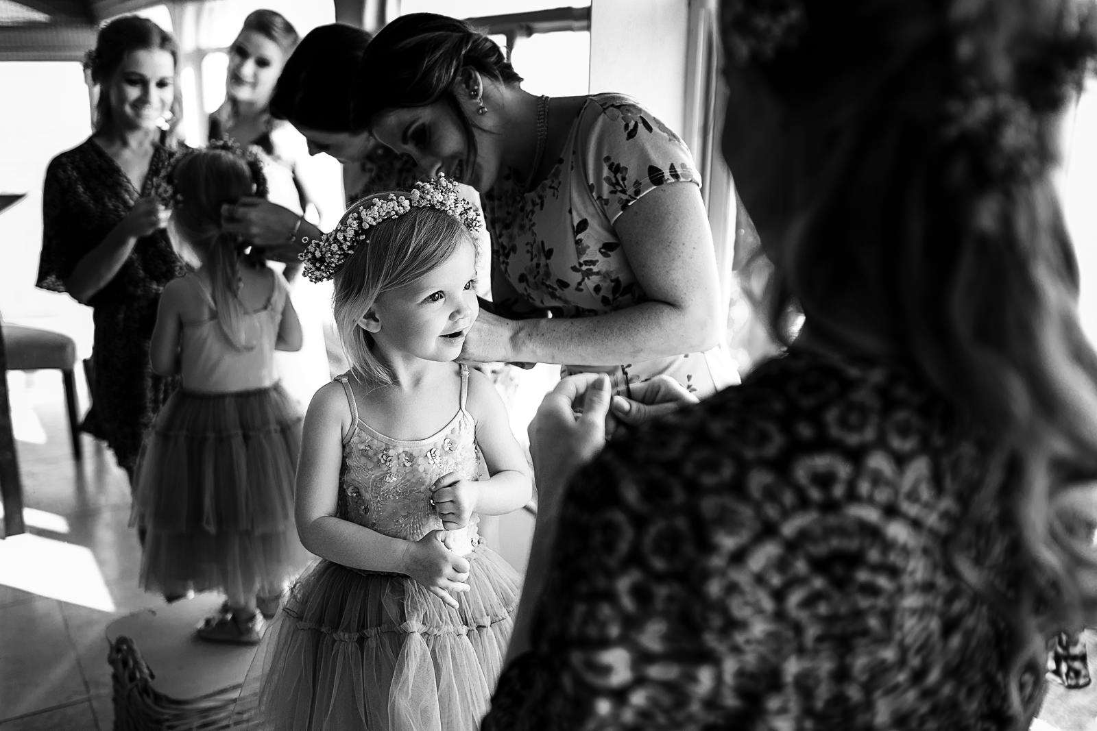 Toddler girl being assisted as preparations for a wedding ceremony