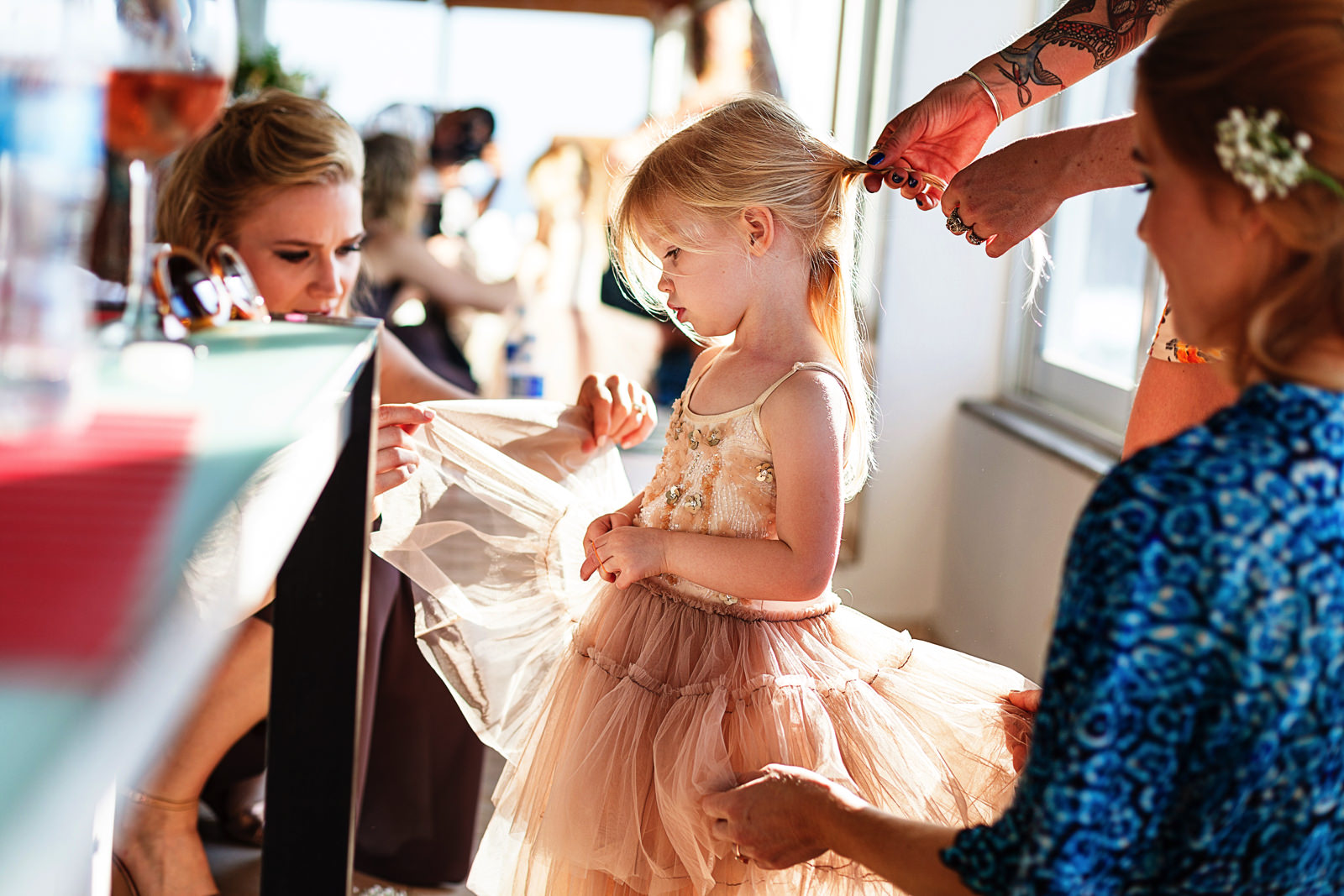Bride and sister helping a toddler girl with hair and dress