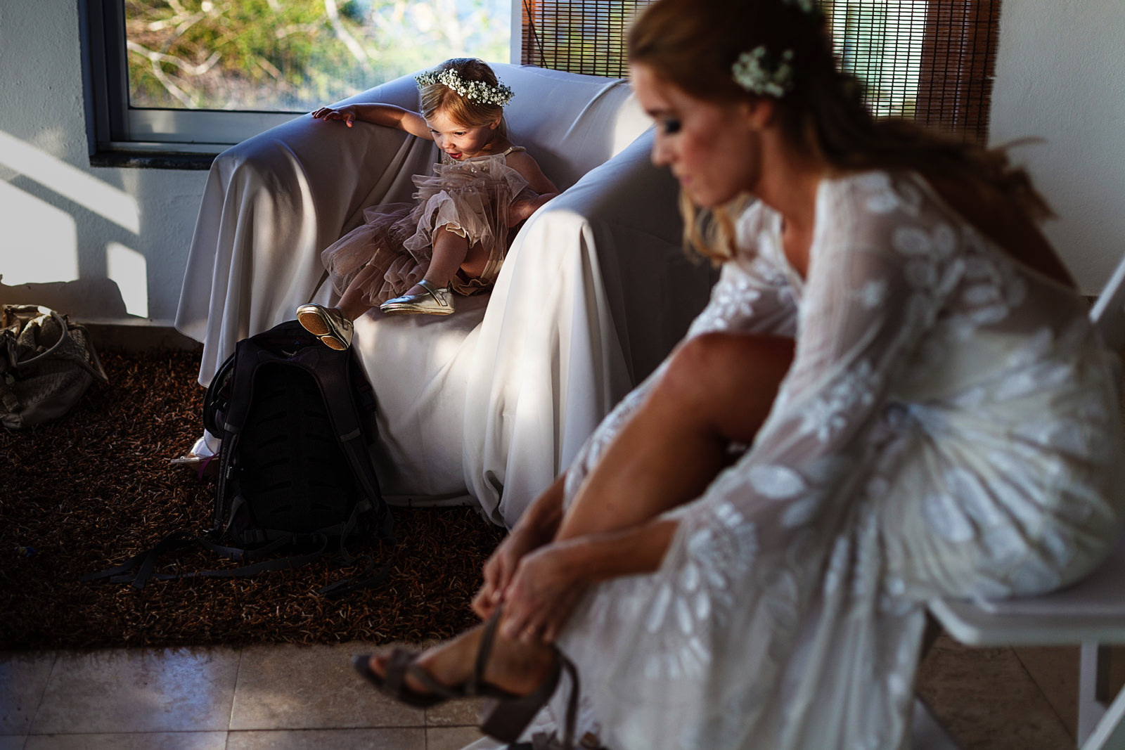 Bride putting her shoes on as toddler girl sits on a couch