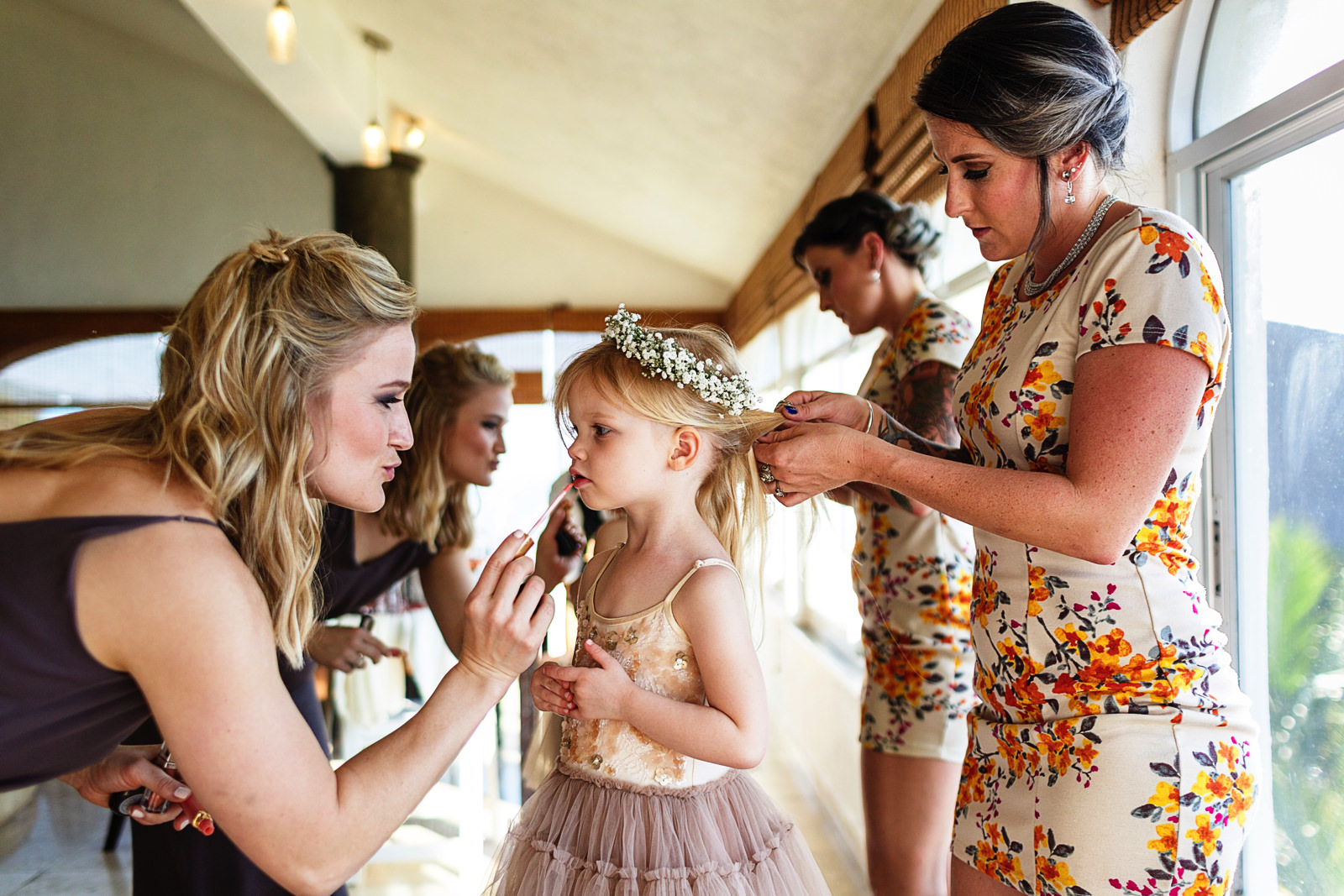 Wedding guest helping toddler girl with lipgloss as another guest is fixing the hair