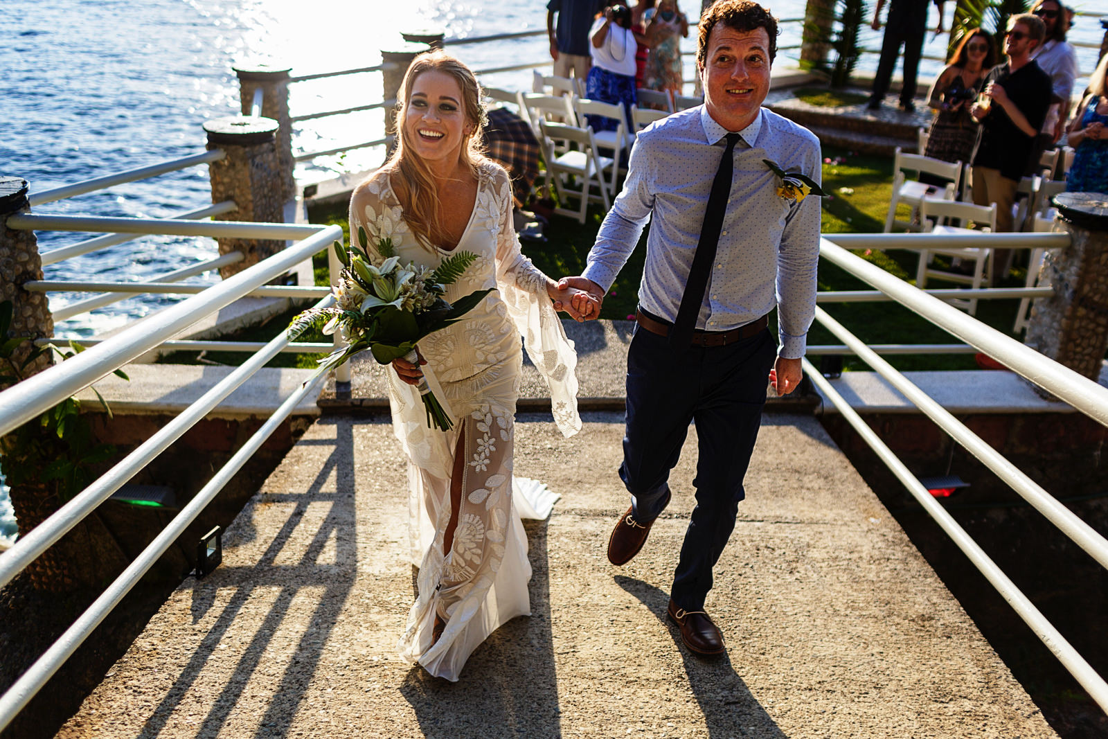 Bride and groom exit the ceremony through the bridge that connects Le Kliff restaurant with the ceremony platform
