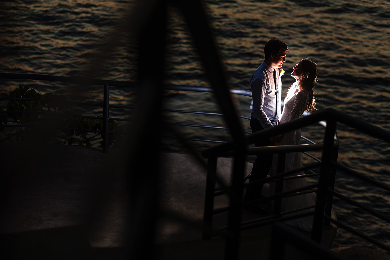 Groom and bride creative portrait against the pacific ocean in Puerto Vallarta, through thehand rails