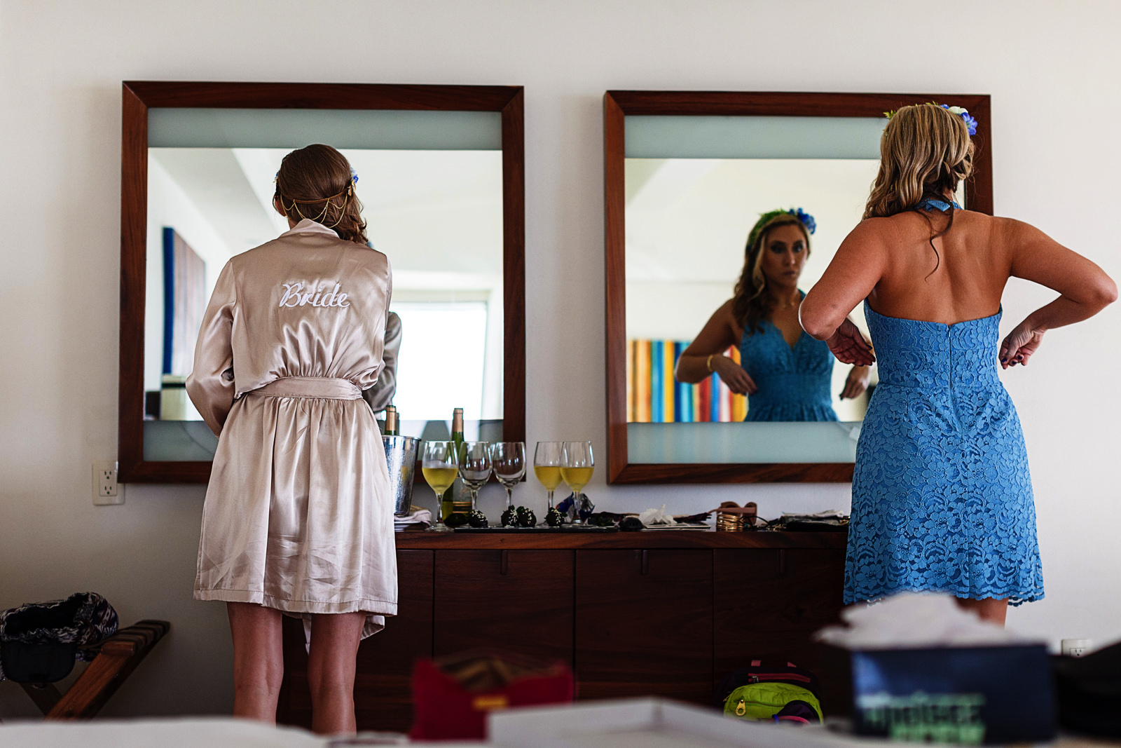 Bride in rope and maid of honor already dressed up in front of the mirrors of the suite bedroom