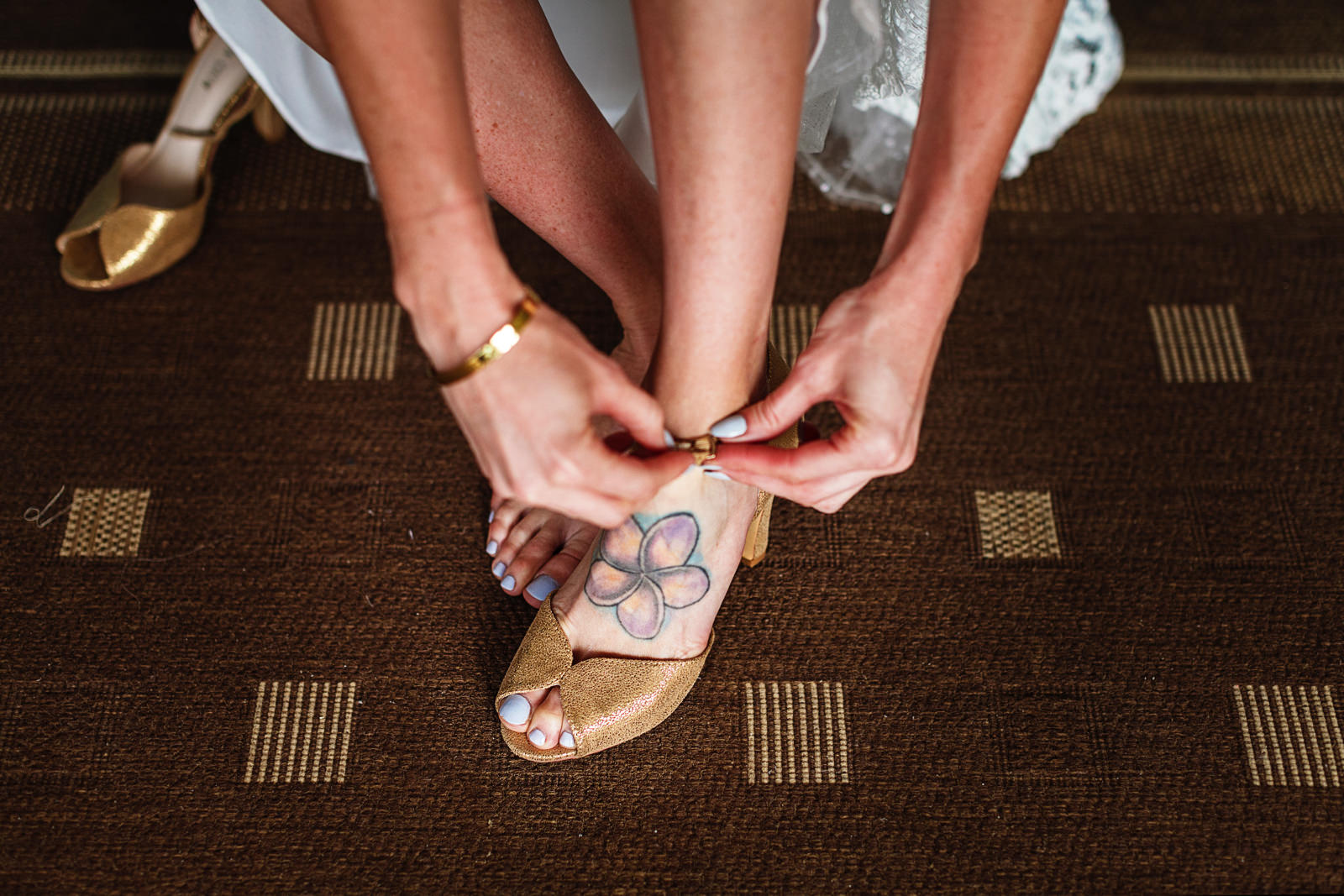 Bride putting her shoes on, a flower tatto on her left foot can be seen