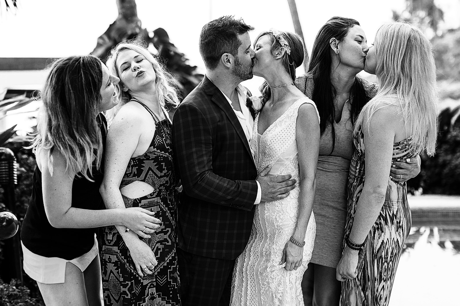 Bride, groom and other guests kissing at the same time