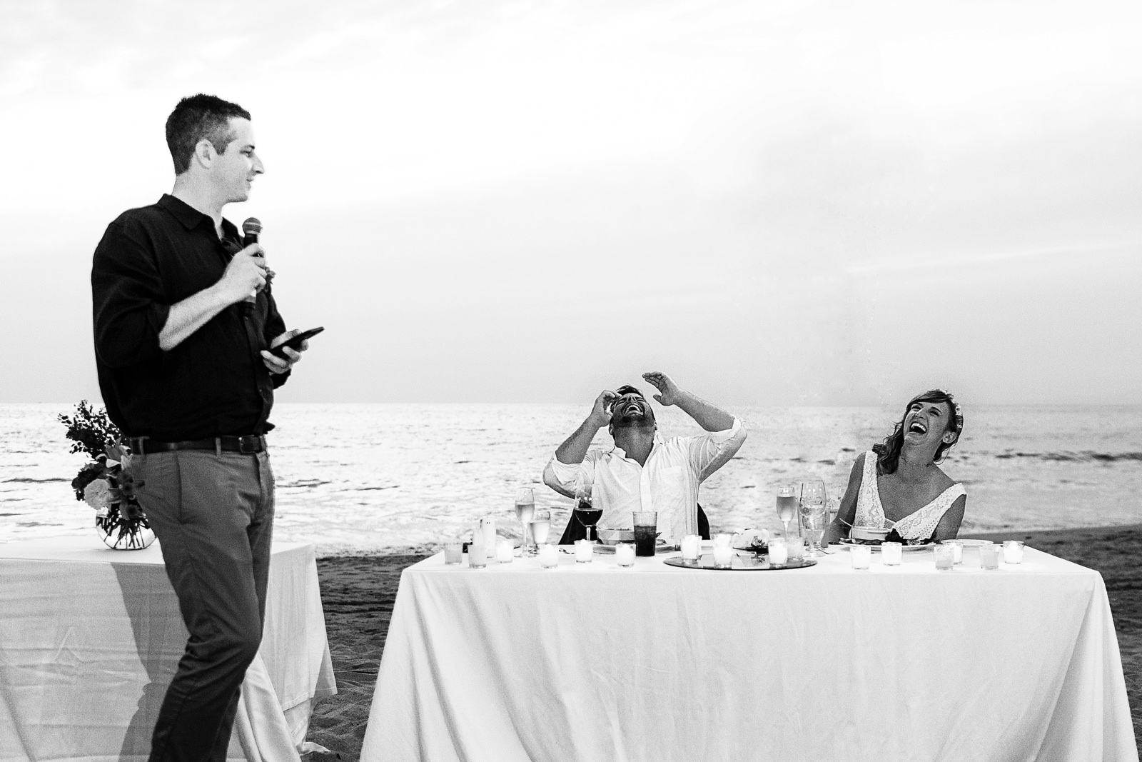 Bride and groom laugh during best man's speech