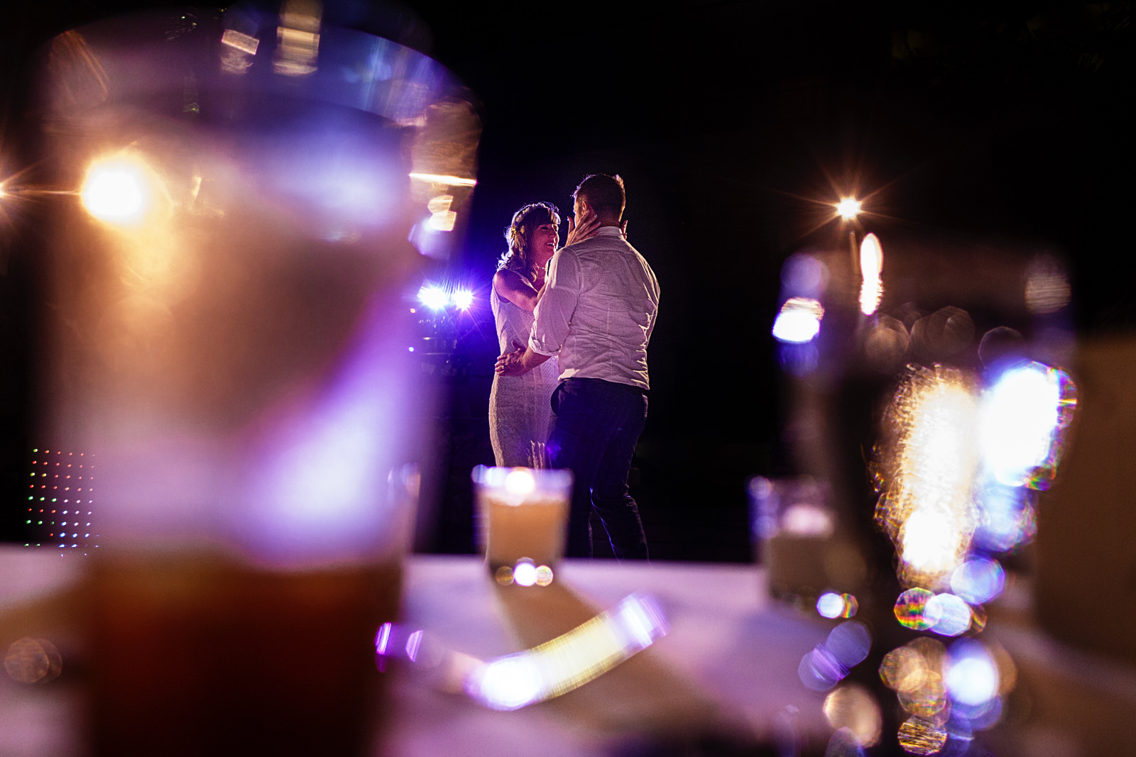 Groom and bride dance through some glasses on the table