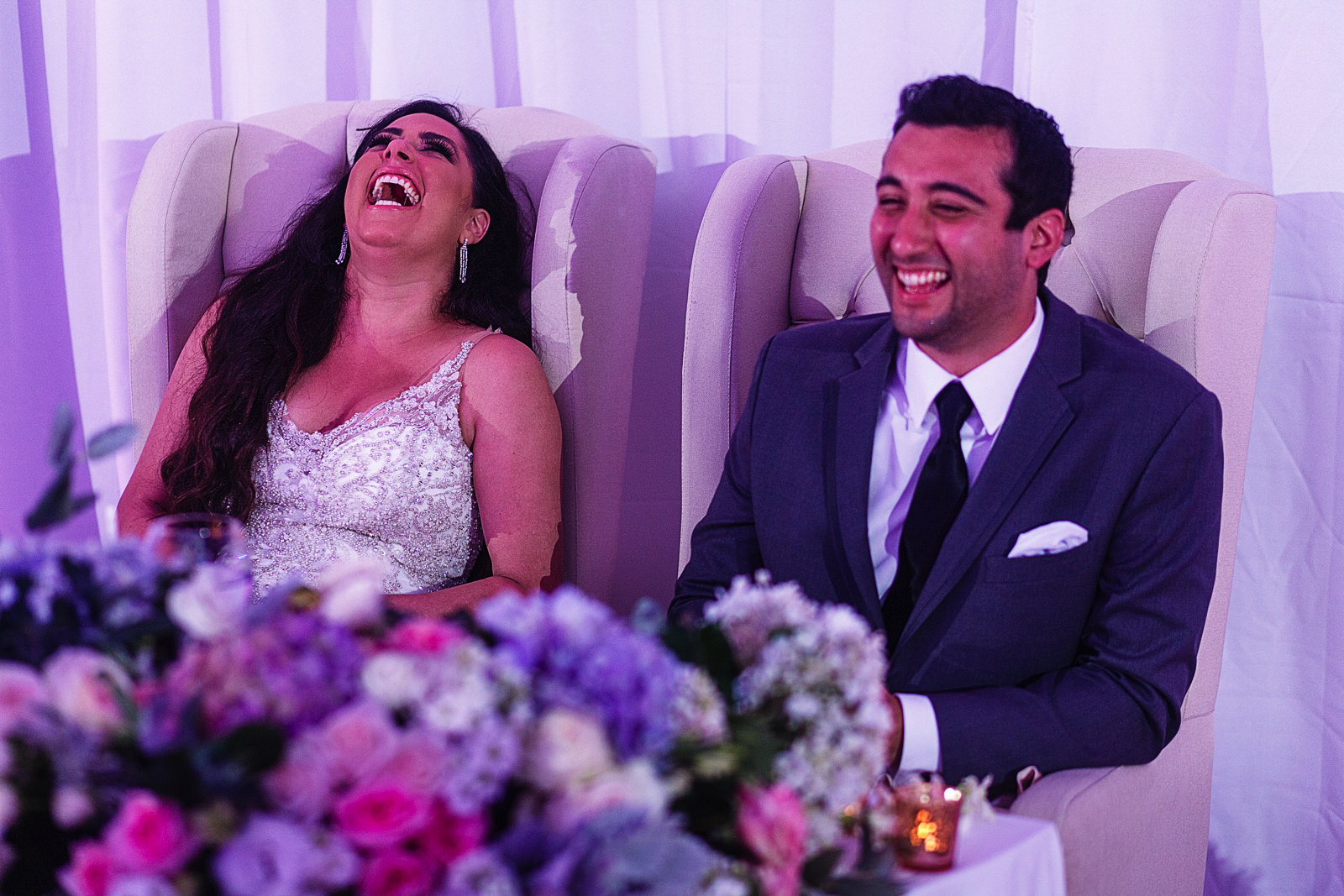 Wedding couple sitting on their table, laugh during the speeches.