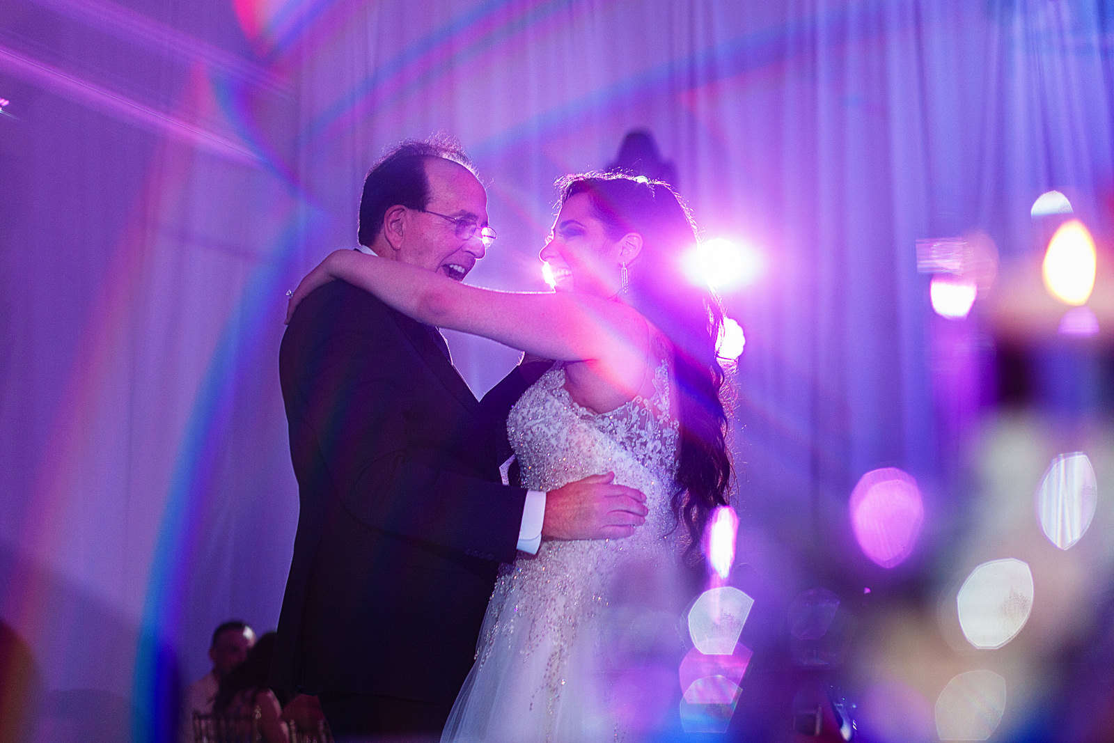 Bride and her dad dancing during the wedding reception, image taken through a prism.