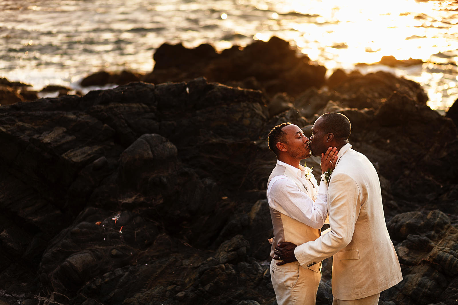 Gay couple kissing on the rock at the casa Karma beach in Puerto Vallarta