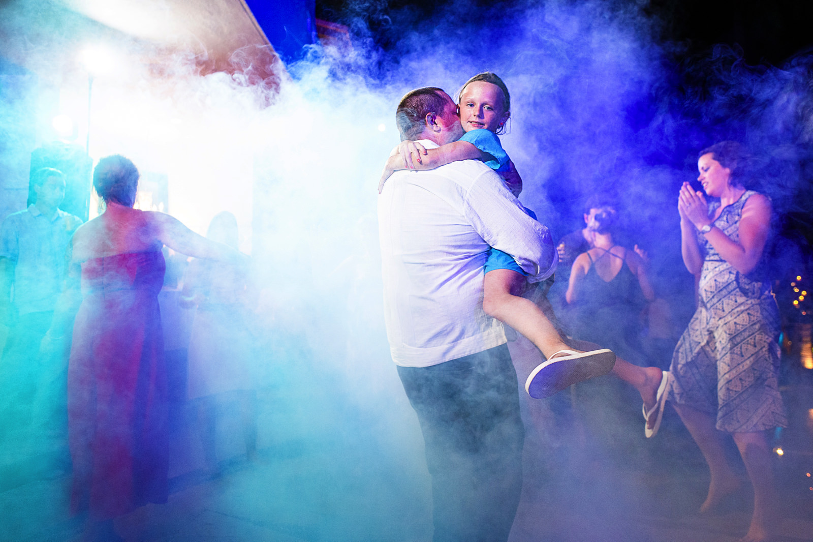 Groom carries her daughter in the middle of the dance floor between smoke and color lights from the DJ