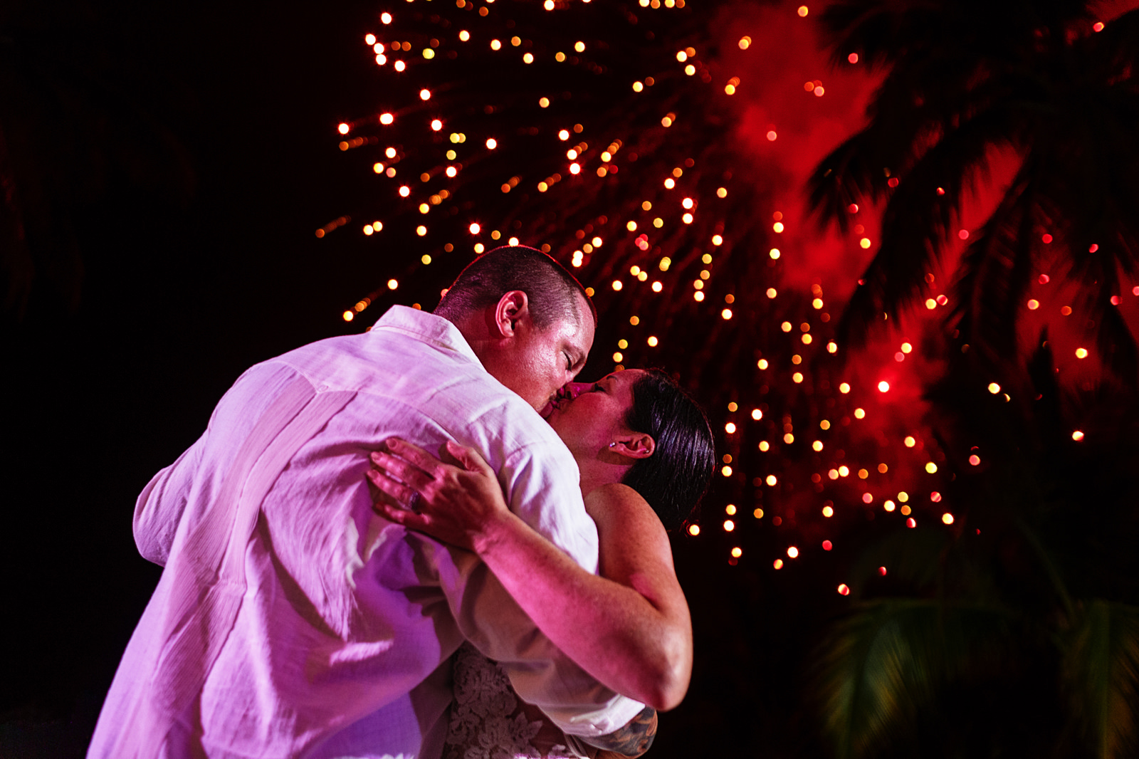 Fireworks in the sky while wedding couple kiss at the end of their first dance as a married couple