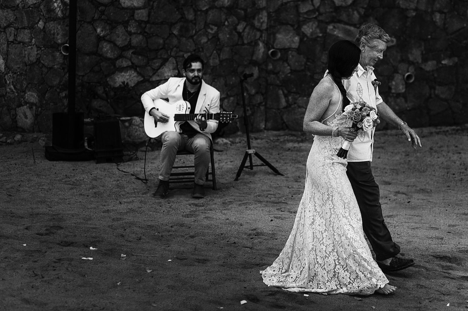 Father of the bride walking his daughter while a guitar player plays in the background