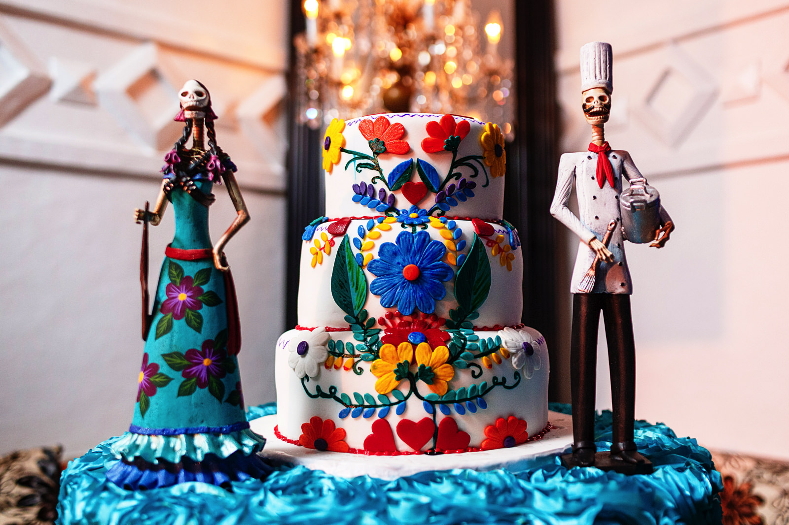Mexican styled wedding cake with two skeleton statues beside it