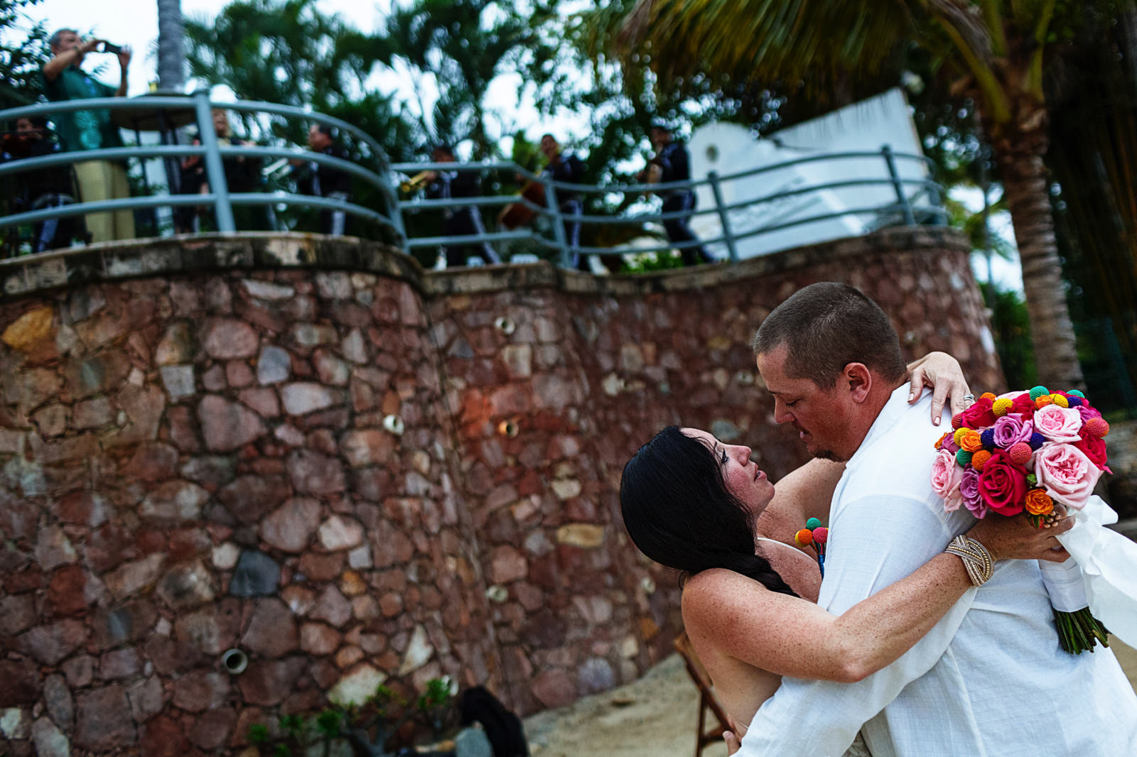 Bride and groom look at each other after their destination wedding ceremony with a mariachi band in the background