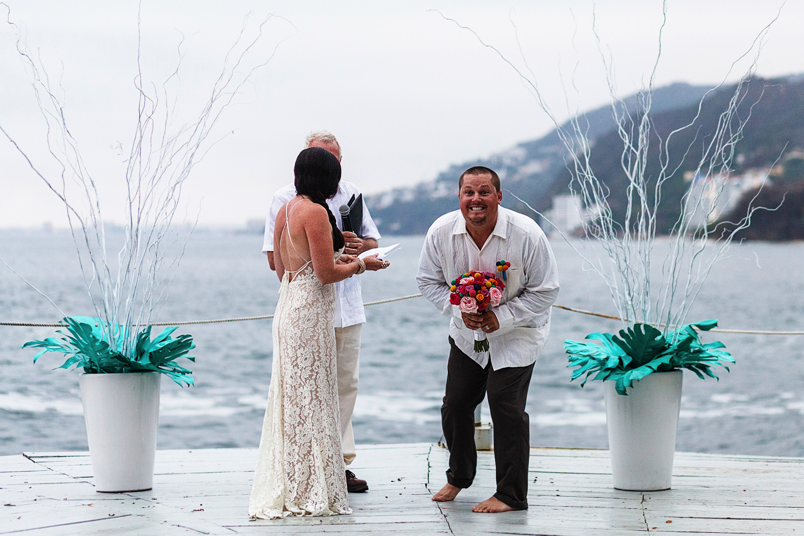 Groom takes the bouquet and smiles at the wedding guests as he turns to them