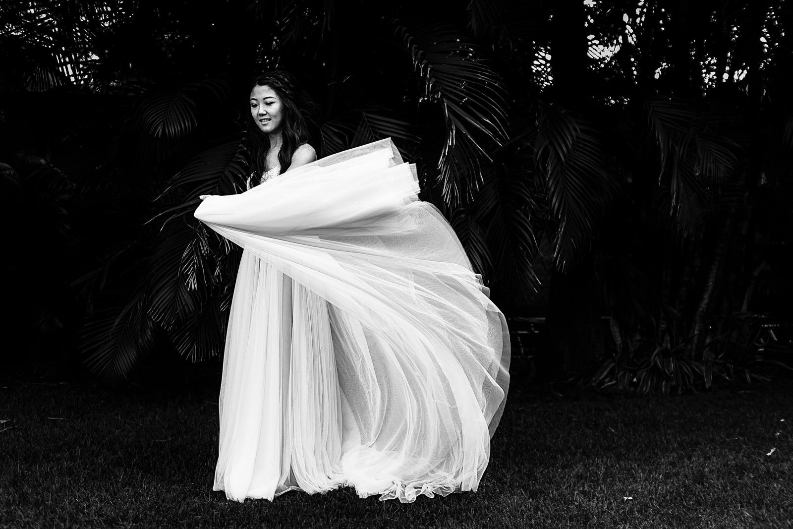 Bride plays with her dress in front of the palm trees at the garden of Martoca.