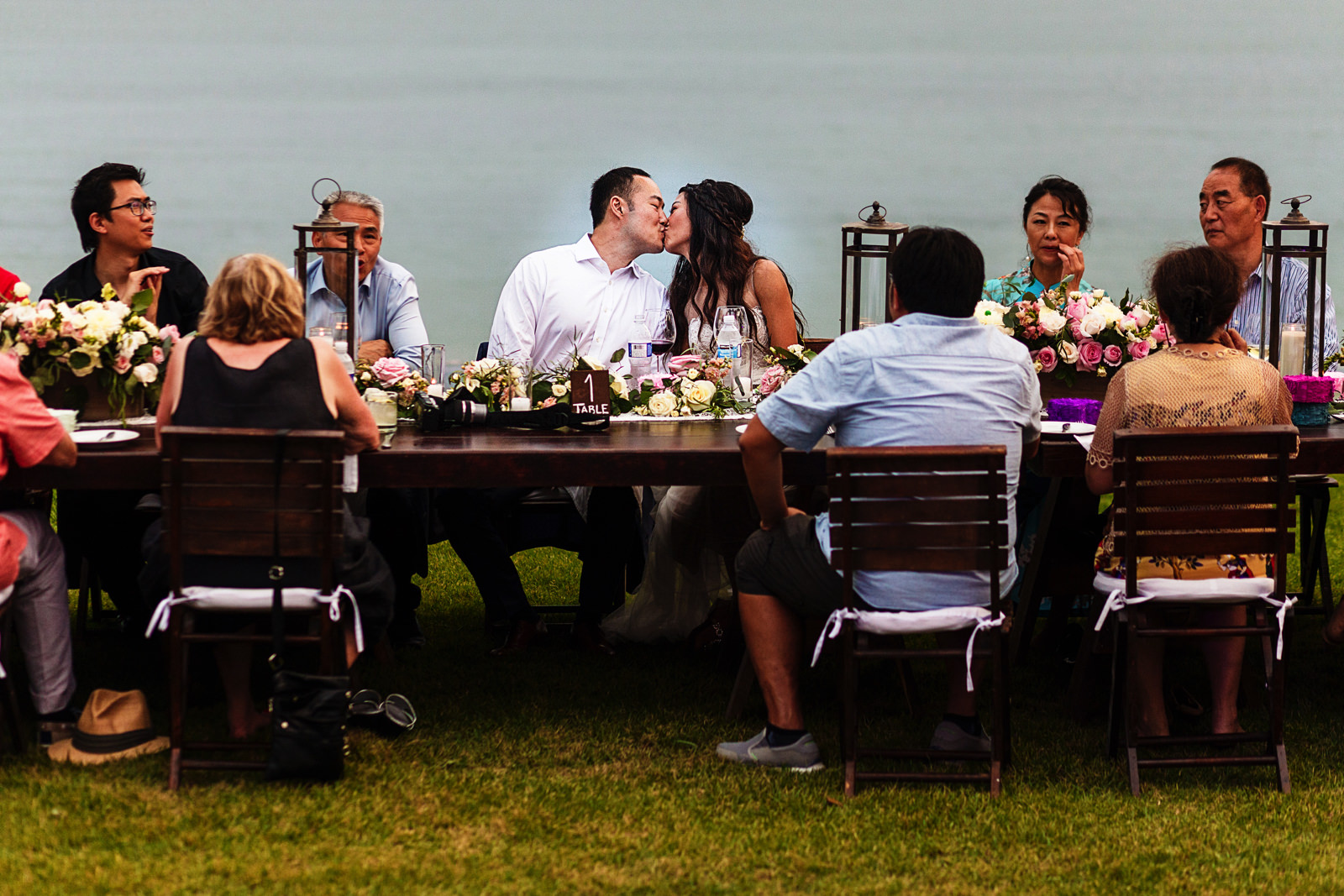 Groom and bride kiss while sitting at the table while dinner is about to begin.