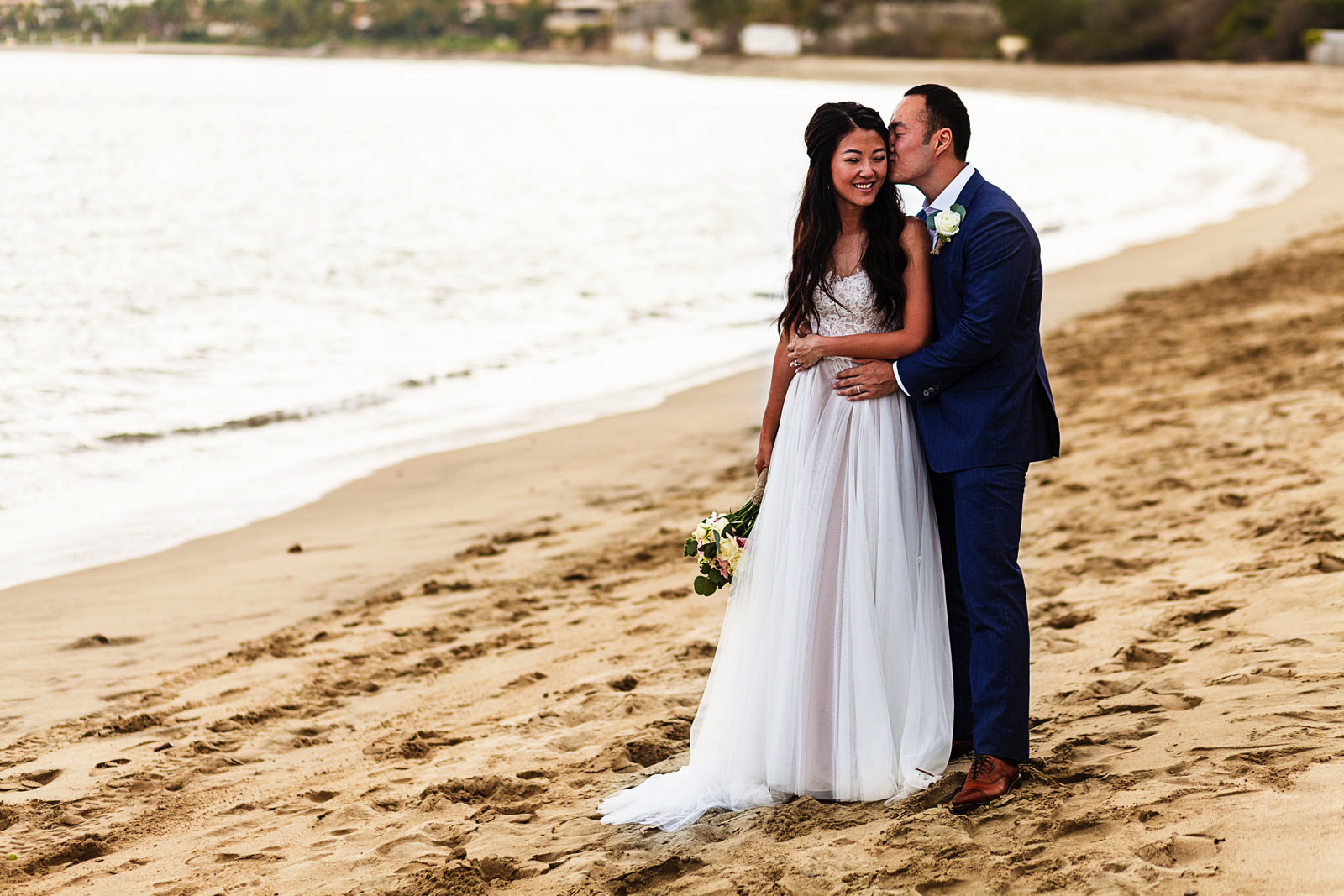 Groom and bride standing on the beach at Bucerias near the ocean.