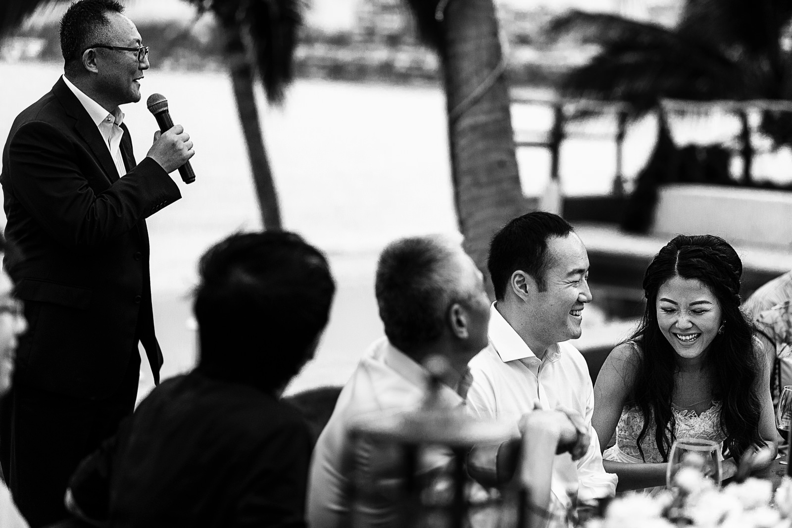 Groom and bride laugh while father of the bride gives a speech.