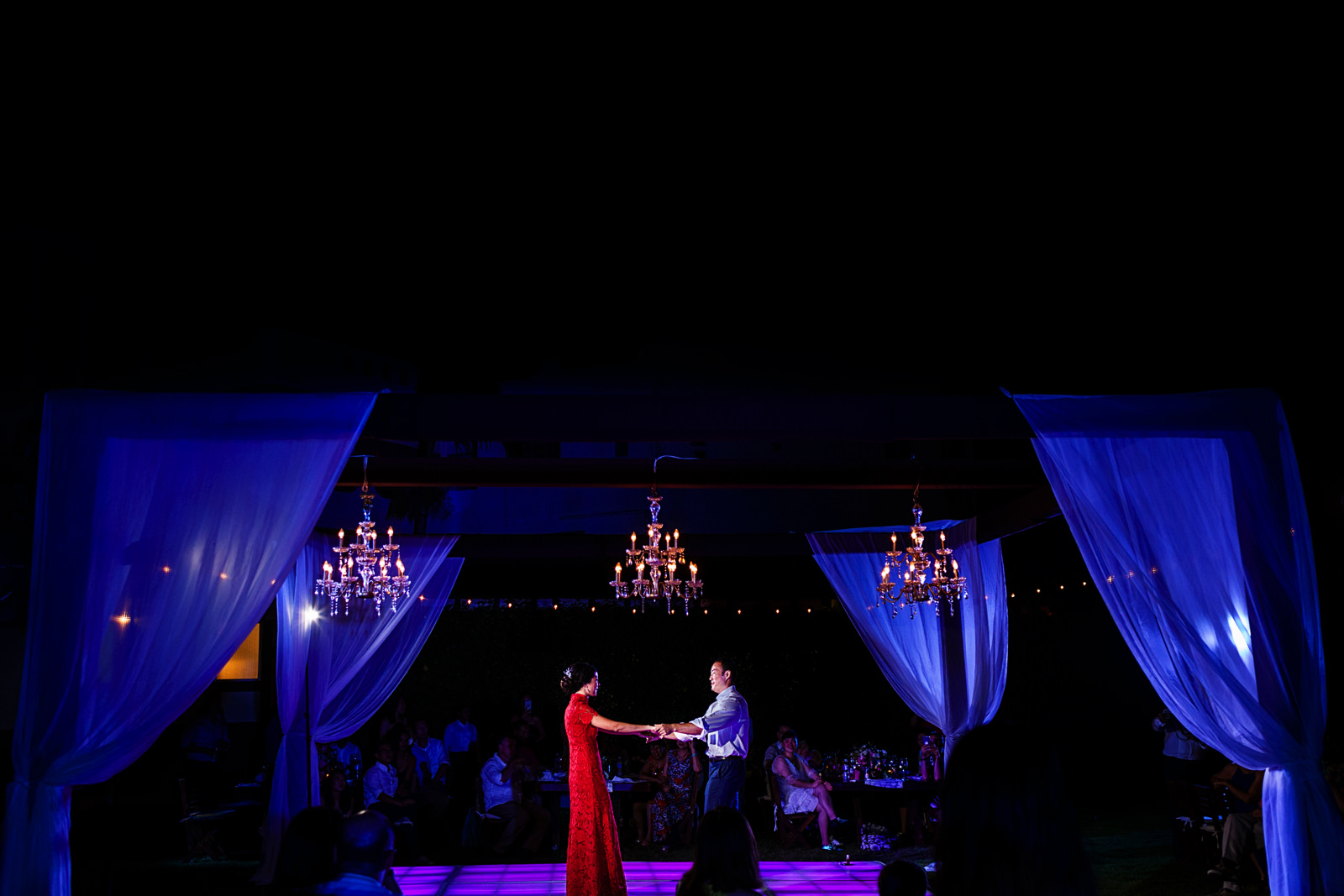 Groom and bride have their first dance as a married couple at the dance floor under a structure with chandeliers.