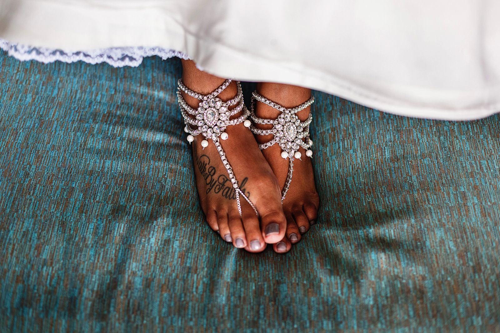 The feet of the bride wearing foot sandals over the sofa at a Hyatt Ziva bedroom