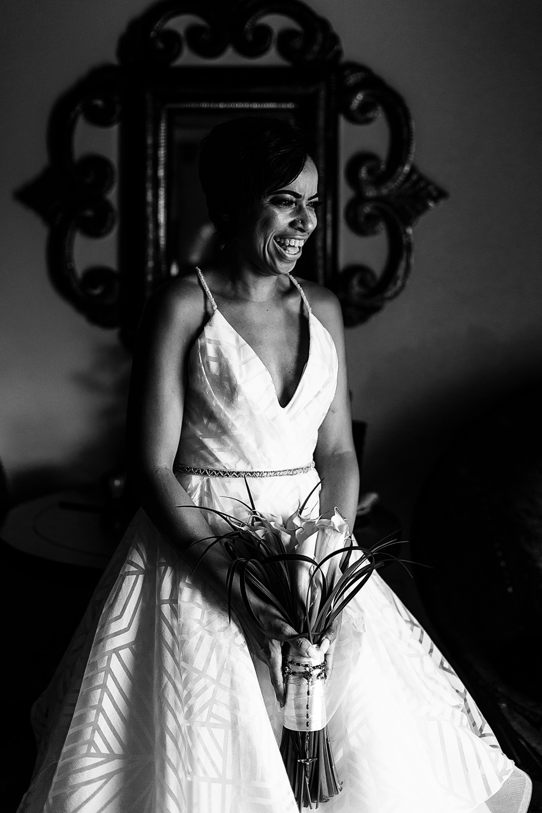 Bride standing near a window for a portrait while laughing