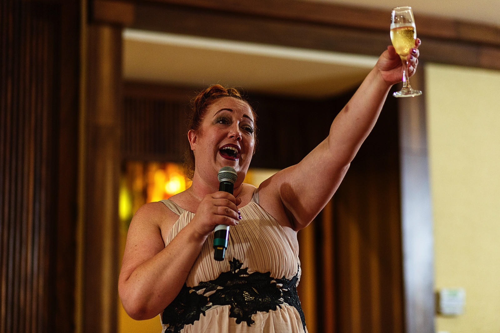 Wedding guest raise her champagne glass at the end of her speech