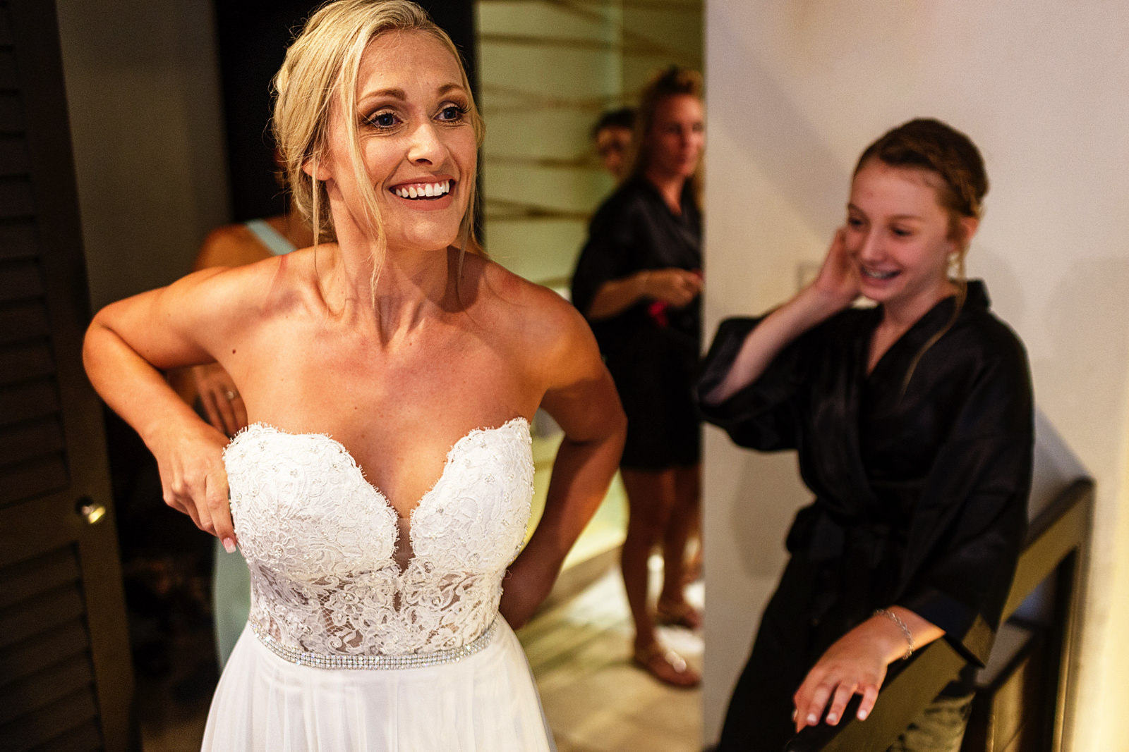 Bride getting into her dress, bridesmaids helping her