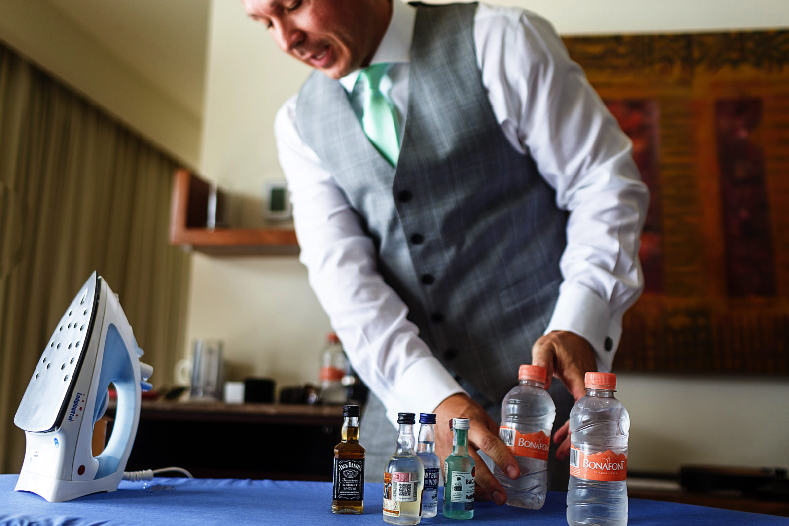 The groom takes all the mini-bottles of alcohol and place them over the ironing table