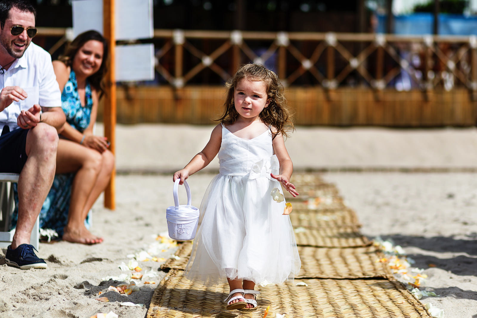 Flower girl walking down the aisle as the wedding ceremony begin on the beach of Mexico
