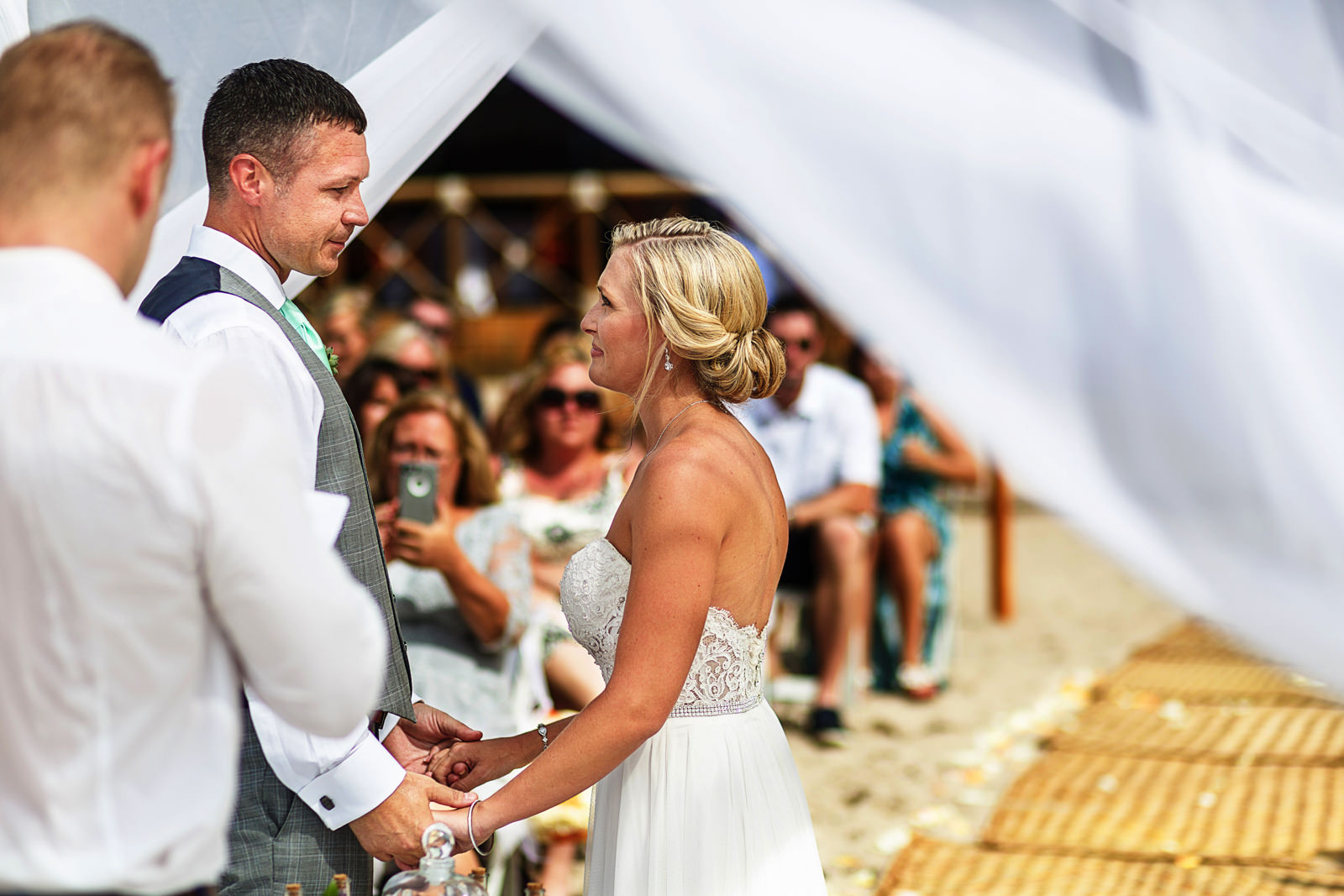 Groom and bride look into each other eyes during their beach wedding ceremony in Mexico