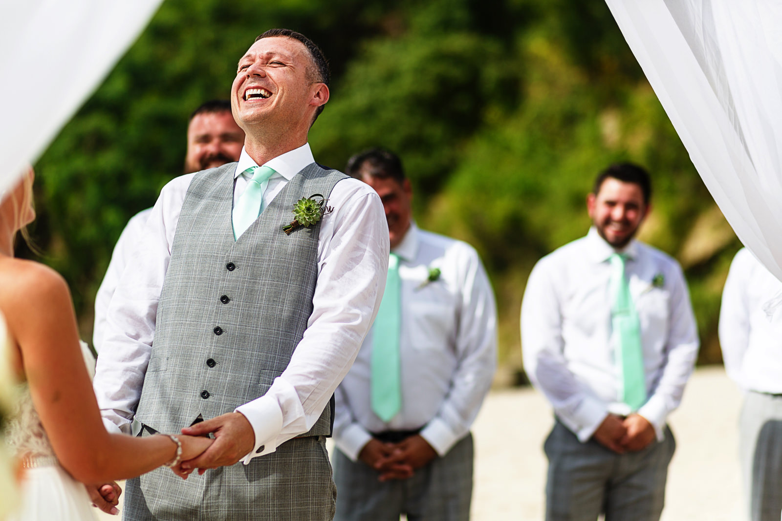 Groom laughing during his wedding ceremony