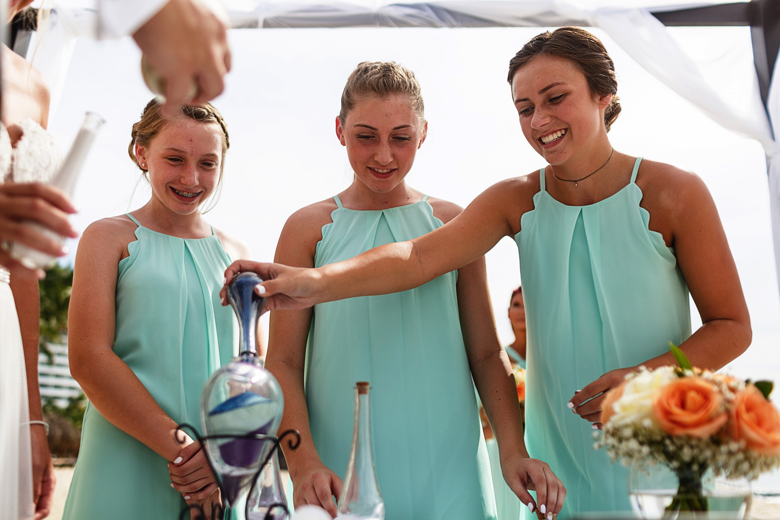 Daughters of the groom and bride filling the container during the sand ceremony on the beach of Mexico