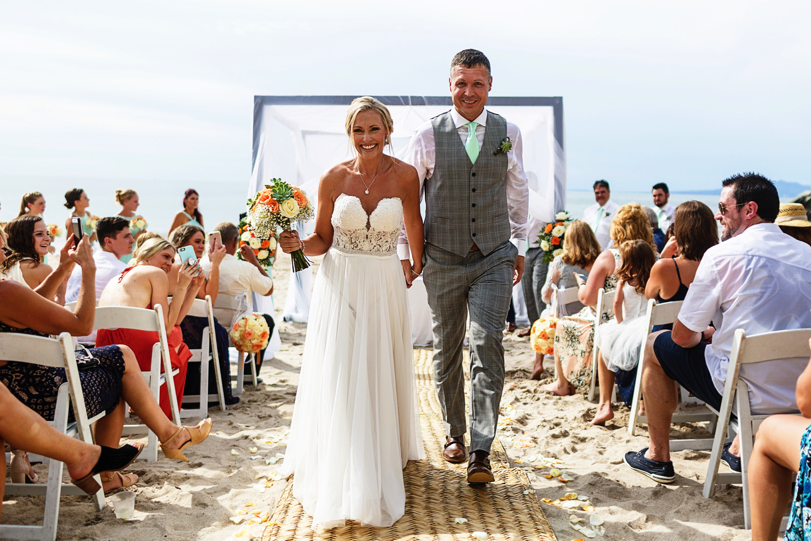 Bride and groom walk out their beach wedding ceremony in Mexico