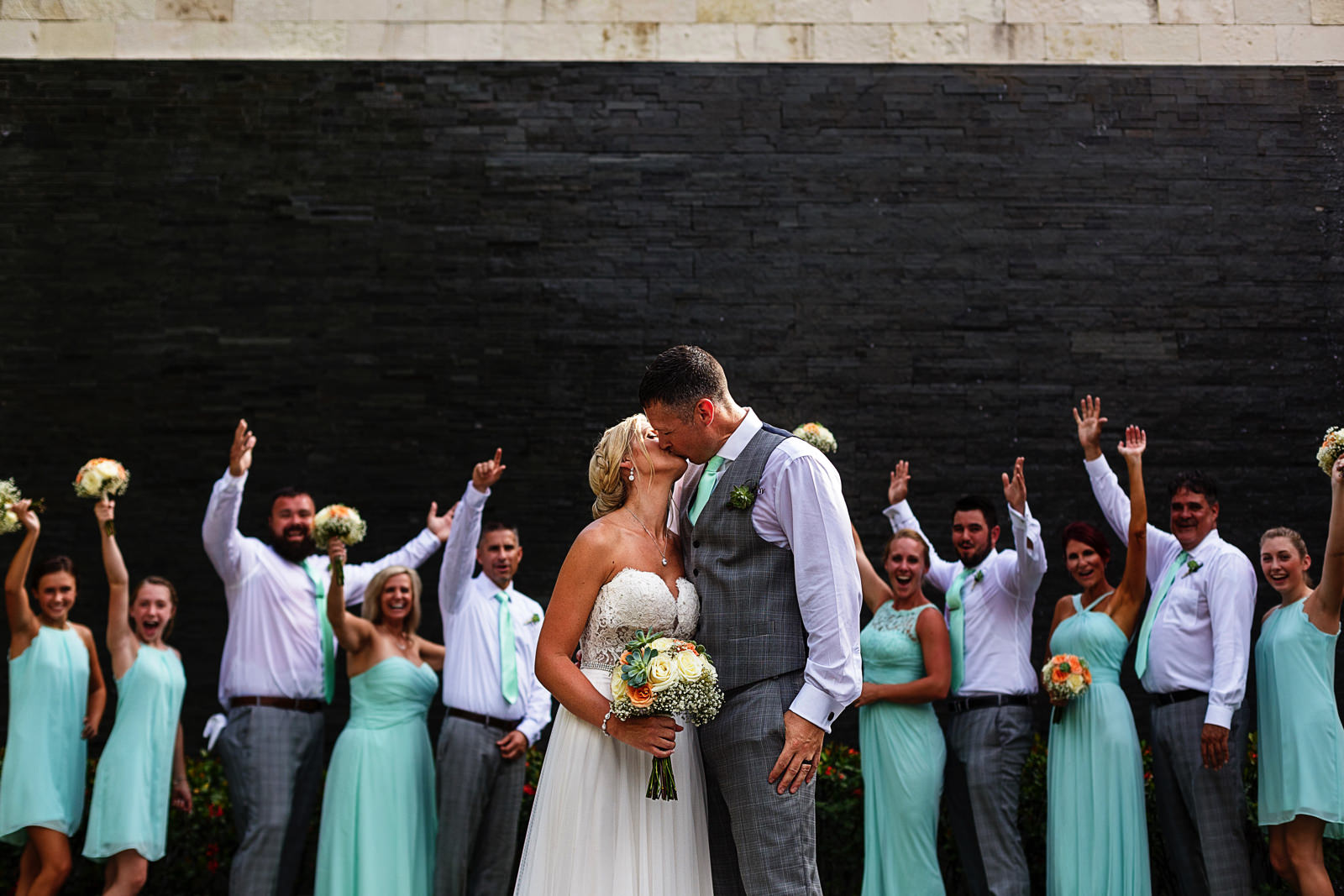 Groom and bride kiss while the groomsmen and bridesmaids cheer for them in the background