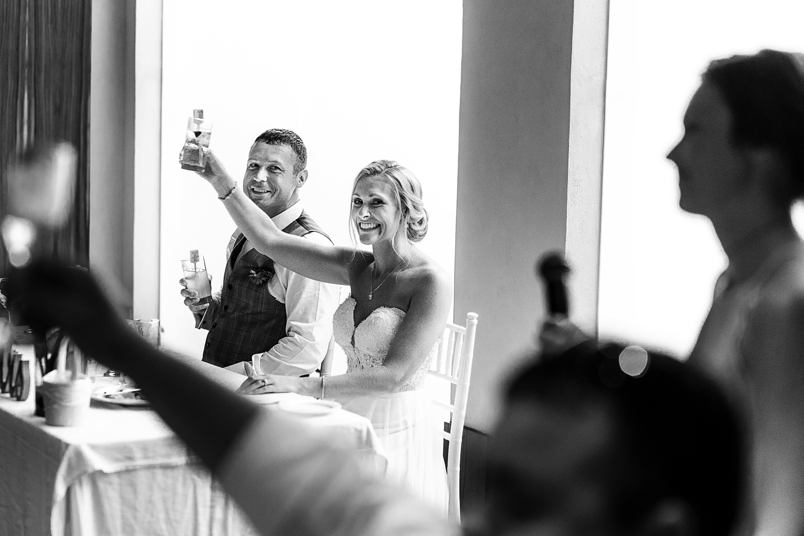 Groom and bride raise their champagne glasses at bridesmaids toast and speech