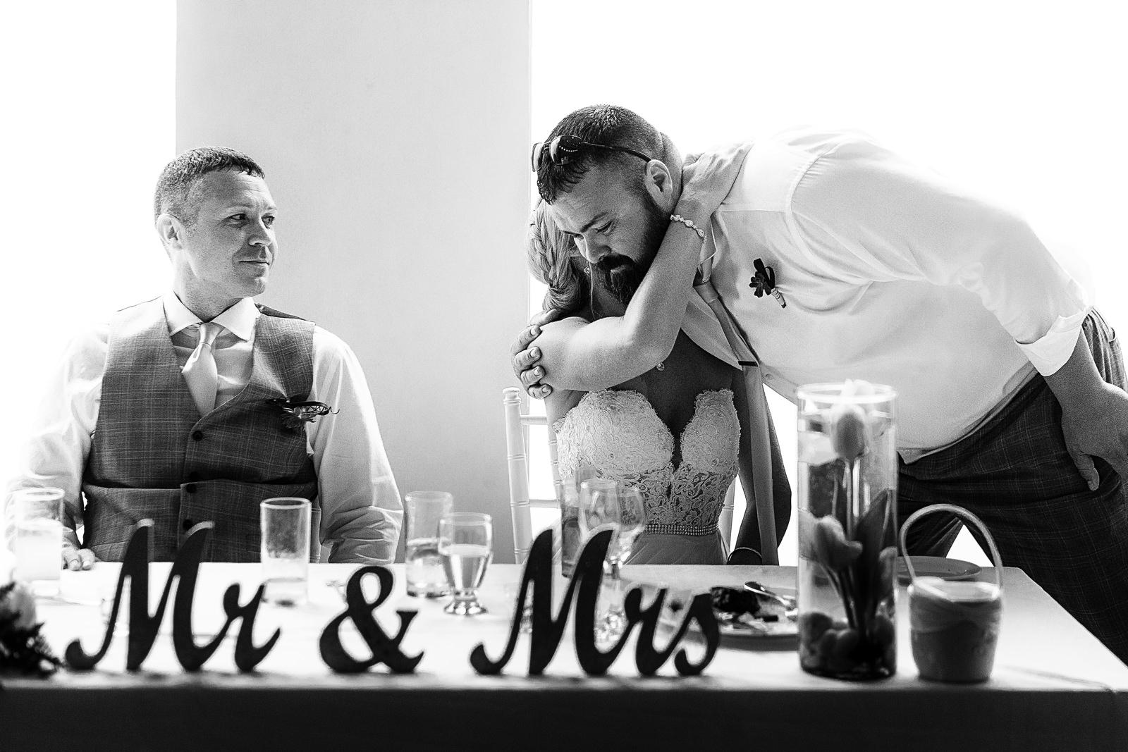 Best man hugs the bride after speech