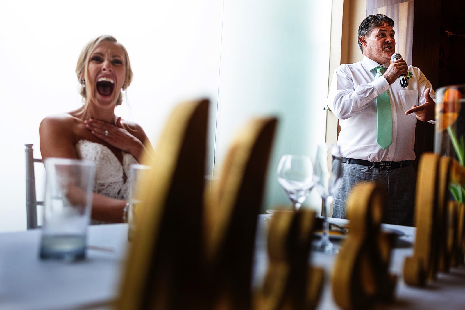 Bride laughs during groomsman speech
