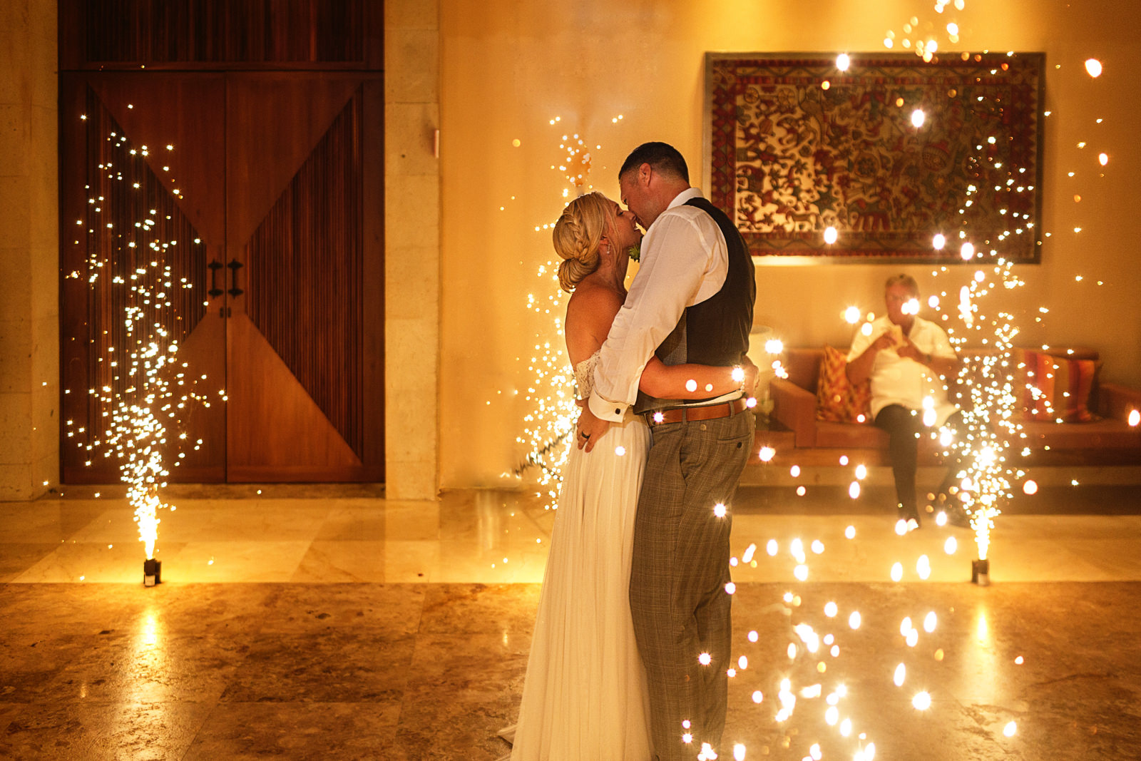 Bride and groom kiss with sparklers around them
