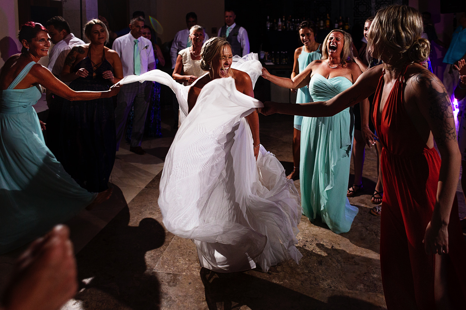 Wedding guests hold and lift the bride's dress in the dance floor