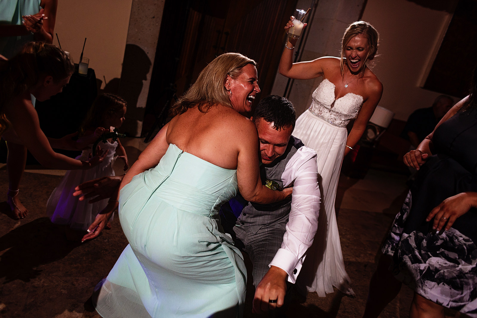 Groom dances with bridesmaid as the bride laughs in the background
