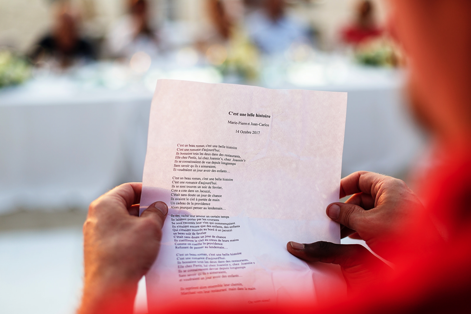 Lyrics of a french song printed and in the hand of a wedding guest