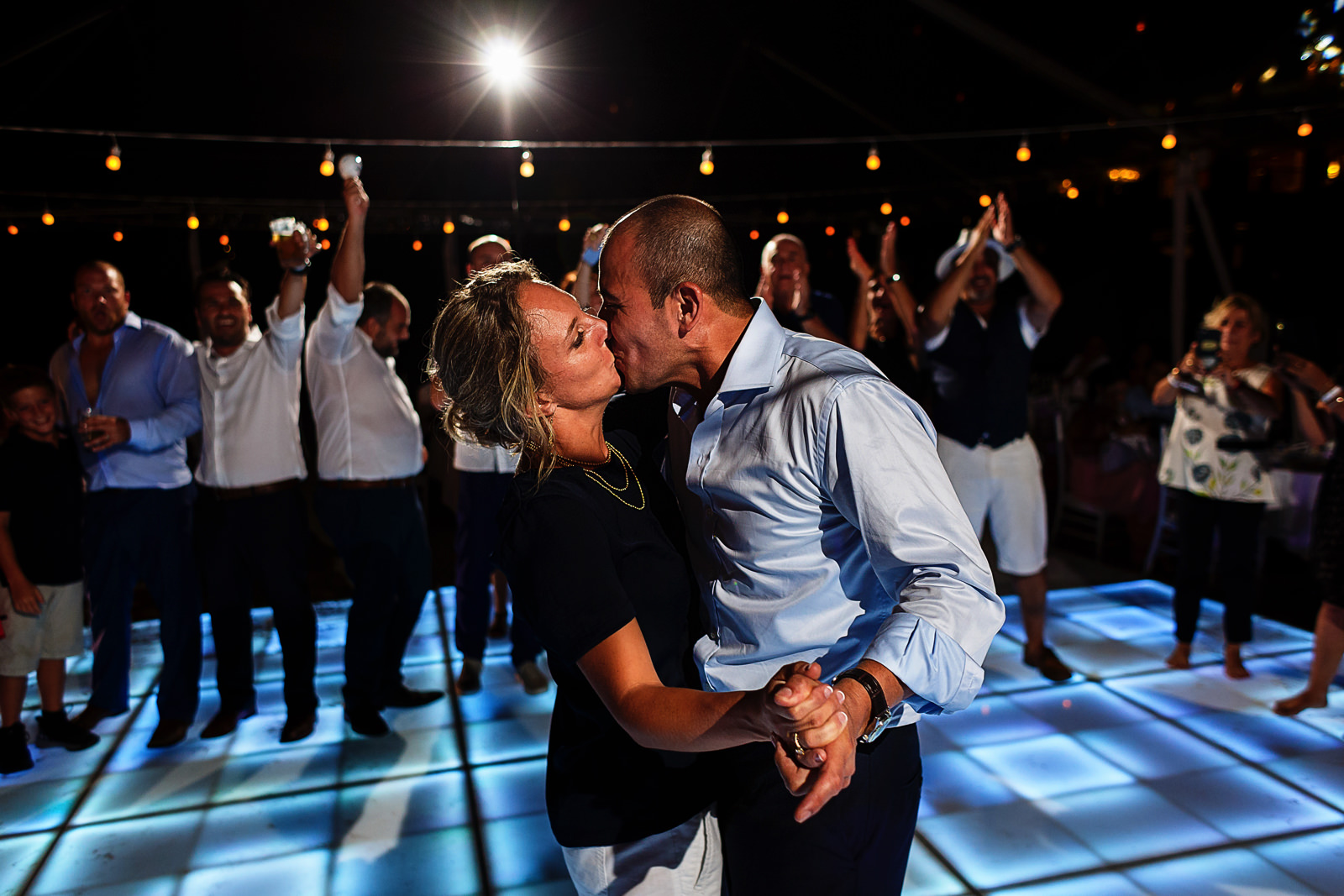 Bride and groom kissing and dancing in front of their wedding guests in the middle of the dance floor