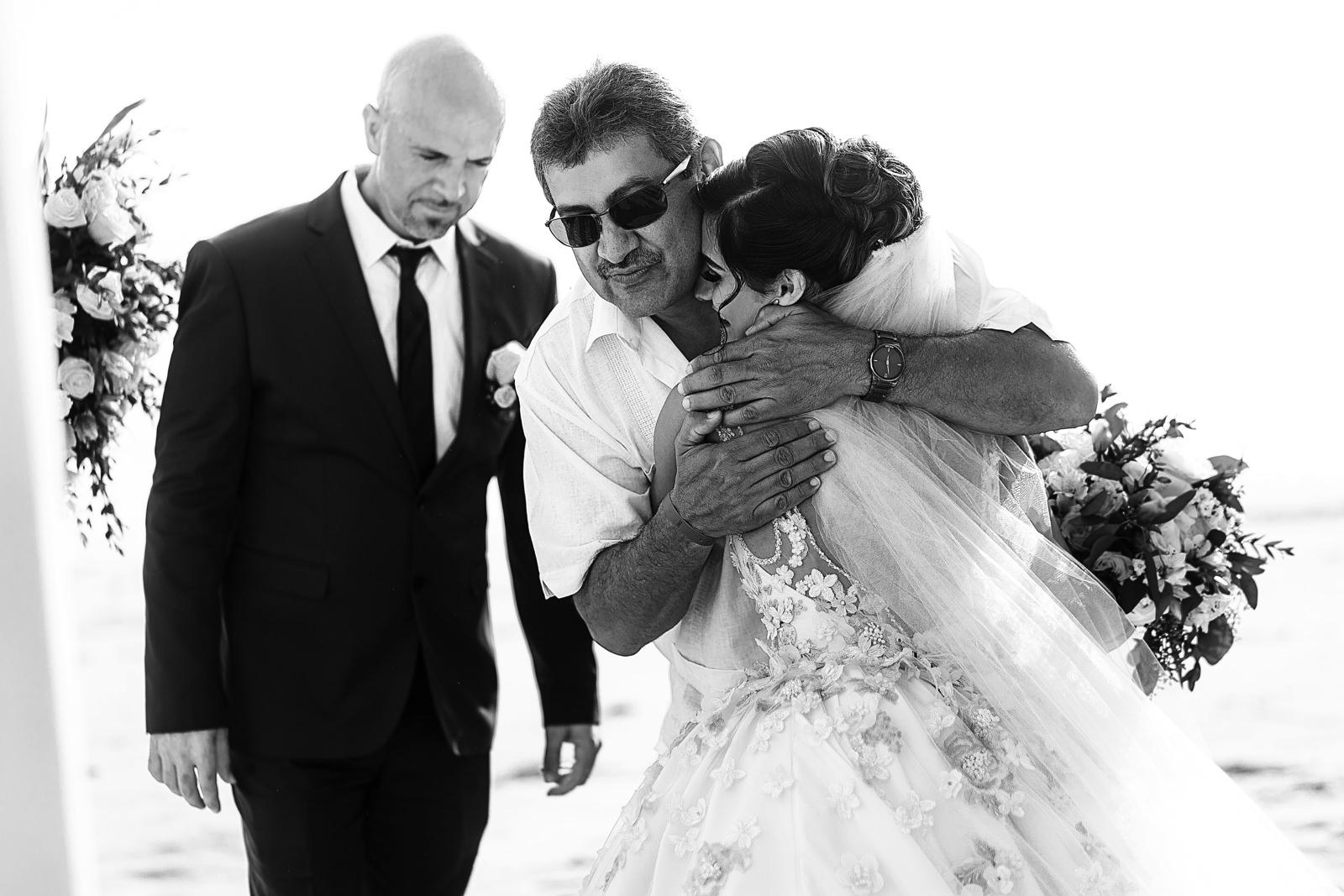 Papá de la novia abraza a su hija al entregarla en el comienzo de la ceremonia de su boda en la playa